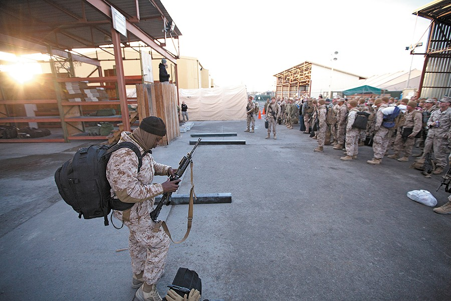 Marine Sgt. Lloyd Beckford checks his rifle during a customs briefing, the first step to going home from a combat deployment in Afghanistan. - YOUNG KWAK