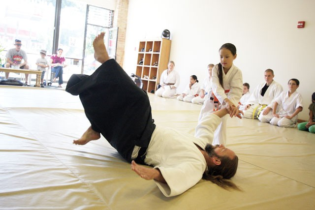 """Marion Sconawah, 7, does a throw on James Landry at the Aiki Institute of Spokane. """"Amazing stuff happens on the mat,"""" says Landry. - YOUNG KWAK"""