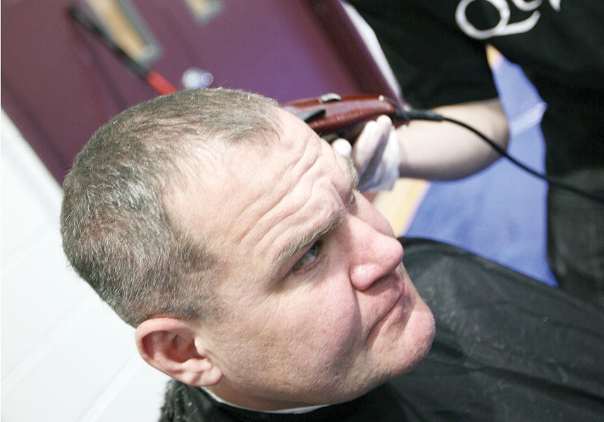 Mark Hunt receives a haircut from Quick\'s Barbershop at Emmanuel Family Life Center. - YOUNG KWAK
