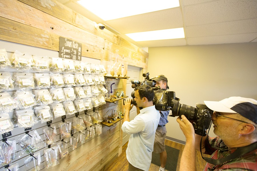 Members of the media photograph marijuana on display at Spokane Green Leaf. - YOUNG KWAK