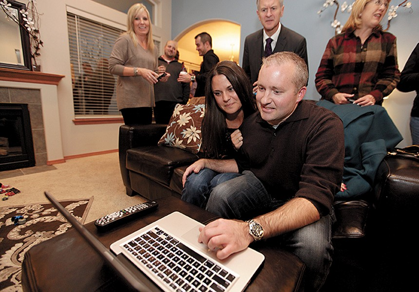 Michael Cannon and fiancée Jodey Miller check early results Tuesday night at their home. - YOUNG KWAK