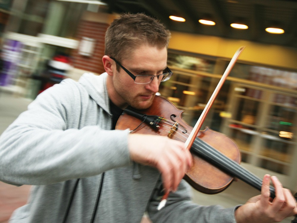 Michael Korpi, Jr. plays his violin to a crowd of busy shoppers. - YOUNG KWAK