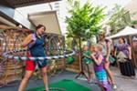 Michelle Heyn, left, of Rock Rings Hula Hoops demonstrates her skill to children.
