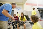 Mountainside Middle School 7th grader Erica Brooks, second from right, receives help from 16-year-old Mt. Spokane High School sophomore Ashley Unruh, second from the left, on a robot before MINDS-i competition. Looking on are teacher David Neale, left, and 7th grader Ali Jones.