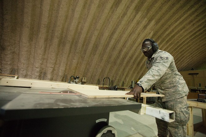 376th Expeditionary Civil Engineers Airman First Class Michael Mills rips wood at his shop. - YOUNG KWAK