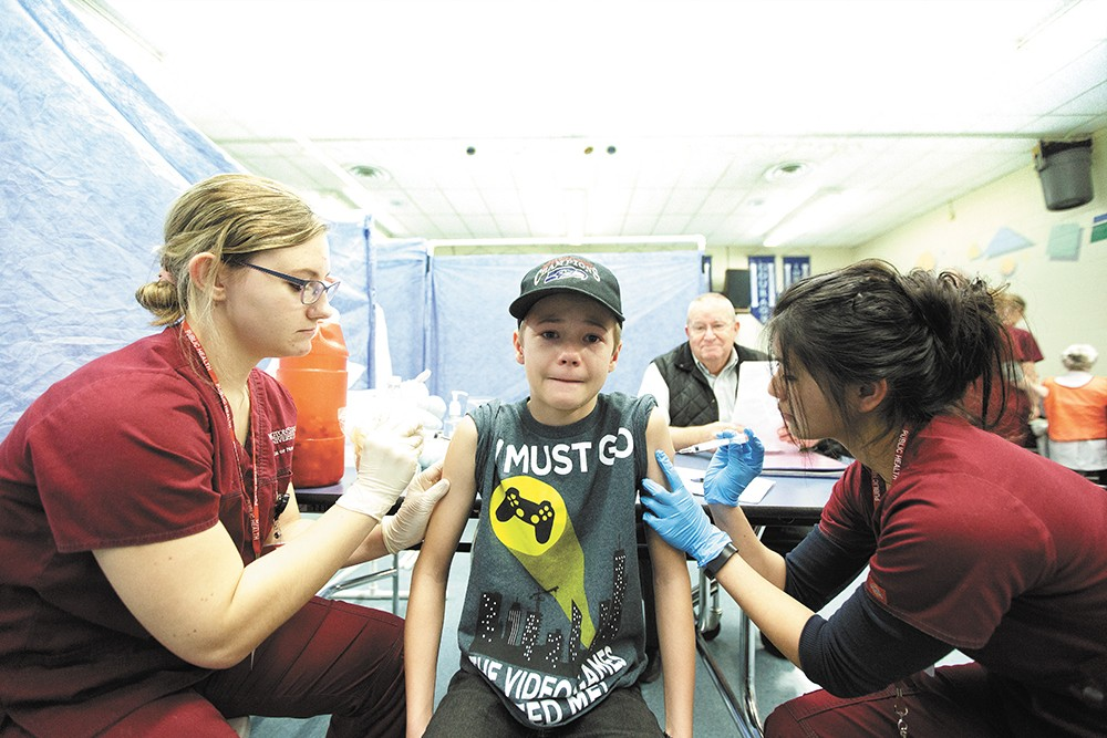 Nursing students immunize 11-year-old James Port during a free vaccine clinic organized by the Spokane Regional Health District. - YOUNG KWAK
