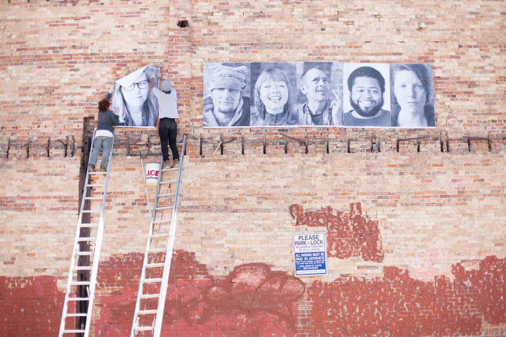 Organizer Susan Jane Hall, left, and volunteer Jose Villa paste a photograph of Laura onto a wall. - YOUNG KWAK