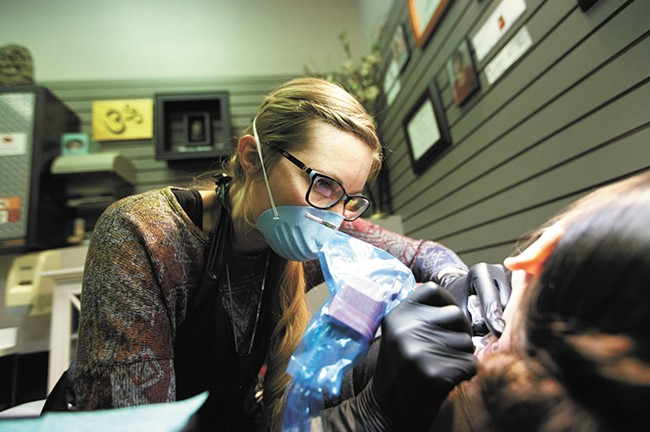 Owner Jacque Gibson Kloehn works to remove a tattoo from Evelyn's neck at Silver Safari in the Spokane Valley Mall. - YOUNG KWAK