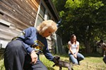 Owner Nancy Taylor, left, plays with two 5-week-old wolf puppies, Teto and Ki Lani, as store manager Shelby Brower watches.