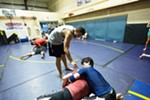 Owner Rick Little, top, shows how to perform a one arm short choke to Eric Higaonna, right, and Daniel Varavin.