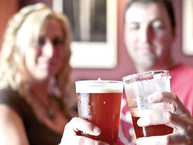 Owner Zeke Sawyer and employee Crysta Hyatt toast before sampling a local IPA at Bag o' Nails Pub. - JORDAN BEAUCHAMP