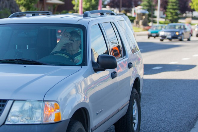 A passing motorist gives a thumbs down to protesters. - MATT WEIGAND