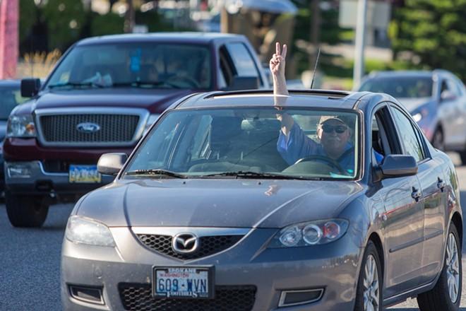 A passing motorists waves a peace sign. - MATT WEIGAND