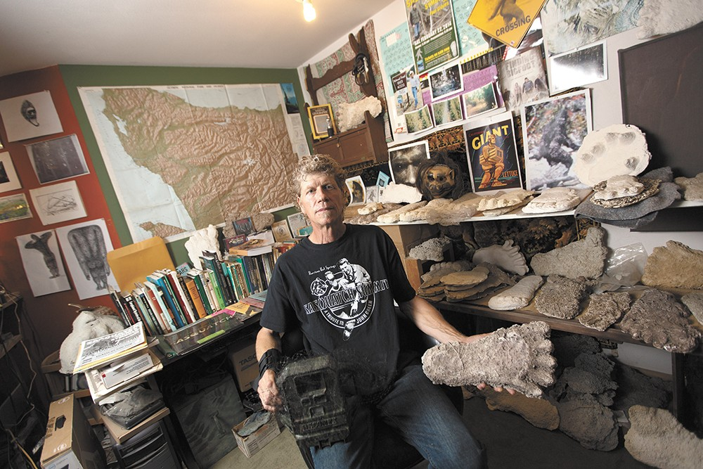 Paul Graves poses at his home in Wenatchee with an infrared camera and his collection of Sasquatch footprint casts. - YOUNG KWAK