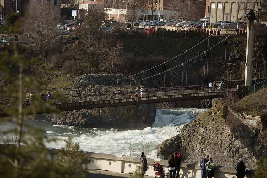 Pedestrians cross the suspension bridge over the raging Spokane River. - YOUNG KWAK