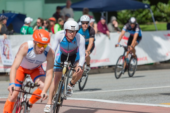 Peter Lorhmann, center, rides through downtown Coeur d'Alene with other competitors as they begin their second lap of the 112-mile bike race. Lorhmann finished in 10:26:12, 90th overall. - MATT WEIGAND