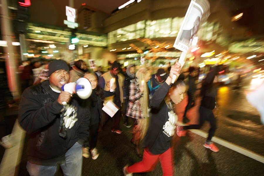 Phillip Baker, left, chanting into a megaphone and Lanae Dedmond, center, walk down N. Wall St. - YOUNG KWAK