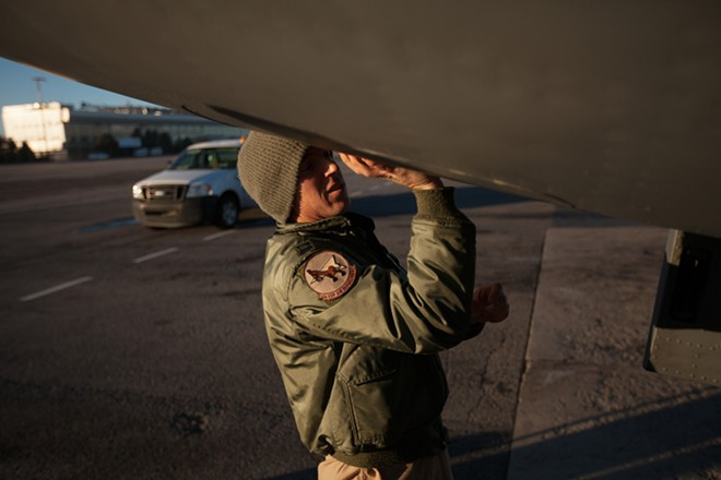 376th Expeditionary Operations Group Pilot and Captain Alex Denton closes a panel on a KC-135 - YOUNG KWAK