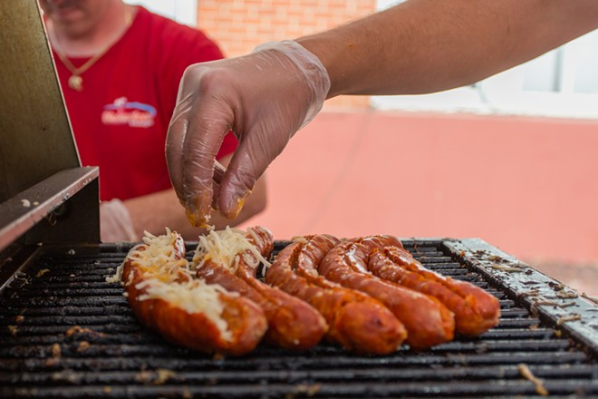 Nick Bokarica, co-owner of Shameless Sausage, stuff cheese in sausages at Food Truck Palooza. - MATT WEIGAND