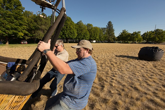 Chaser Dan Torkelson, right, and Pilot and Owner Forey Walter remove the basket from a trailer before a hot air balloon ride. - YOUNG KWAK