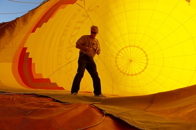 Pilot and Owner Forey Walter pulls on a shroud line as the envelop is inflated before a hot air balloon ride. - YOUNG KWAK