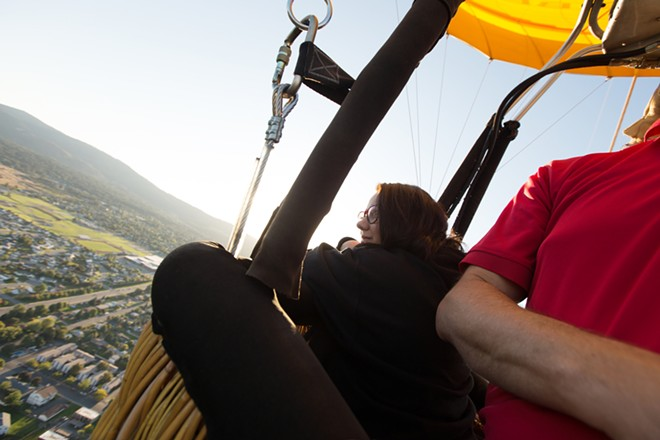 Passenger Tabina Al-Deik looks at the landscape during a hot air balloon ride. - YOUNG KWAK