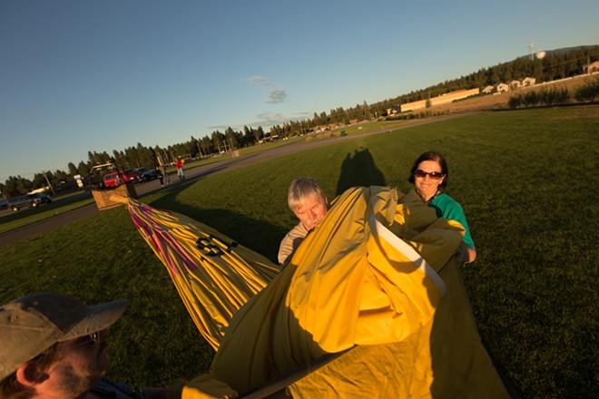 Pilot and Owner Forey Walter, center, packs the envelope into a bag with the help of Chaser Dan Torkelson, left, and Gail Bongiovanni after a hot air balloon ride. - YOUNG KWAK