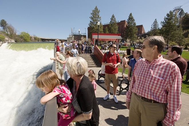 Three-year-old Ava Werner, left, watches the Spokane Falls, while being held by her grandmother Marlys McDermott, center, as her grandfather Mike looks on. - YOUNG KWAK