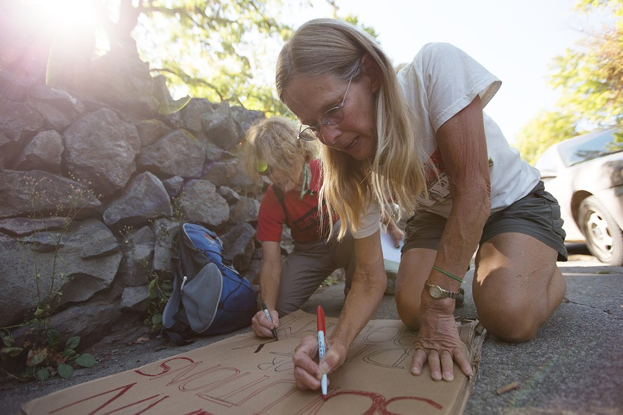 """Anne Stephenson, right, and Barbara Morkill write a sign that states """"Clean Solutions for Dirty Problems"""" before a People's Climate March. - YOUNG KWAK"""