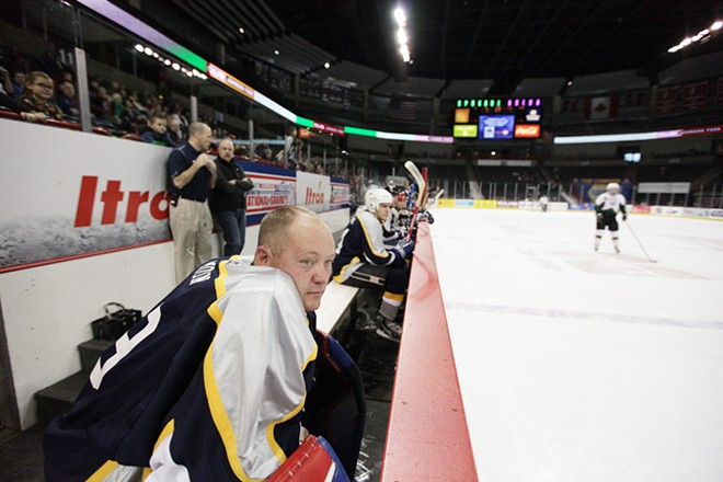 Spokane Police Department Officer Brad Moon watches the third period of a hockey game against the Spokane County Sheriff's Office. Moon is the founder and organizer of the game. - YOUNG KWAK