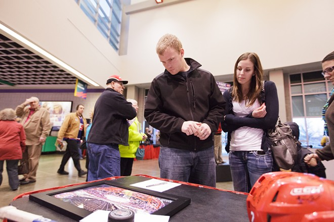 Justin, left, and Heather Arts look at silent auction items after a Spokane Police Department and Spokane County Sheriff's Office hockey game. - YOUNG KWAK