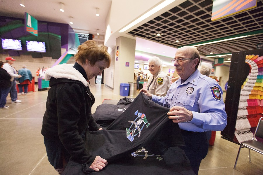 Spokane Police Department Community Volunteer John Silano, right, shows Mary Freeman a T-shirt after a Spokane Police Department and Spokane County Sheriff's Office hockey game. - YOUNG KWAK