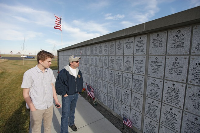 U.S. Navy (Ret.) John Grewell, right, and his 15-year-old son read markers at the Columbarium area at the Washington State Veterans Cemetery. - YOUNG KWAK
