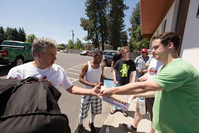 Pizza Rita owner Brian Dickman, left, sells a cheese pizza to Tony Serticchio, right, and Max Cowan, second from the right, outside Spokane Green Leaf. - YOUNG KWAK