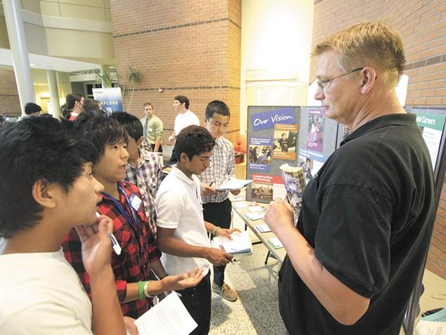 Pranesh Rai, second from left, speaks to Scott Oakshott of the Spokane Skills Center - YOUNG KWAK PHOTO