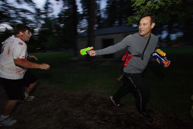 Race participant Jim Carbajal, right, shoots zombie Caleb Heath. - YOUNG KWAK