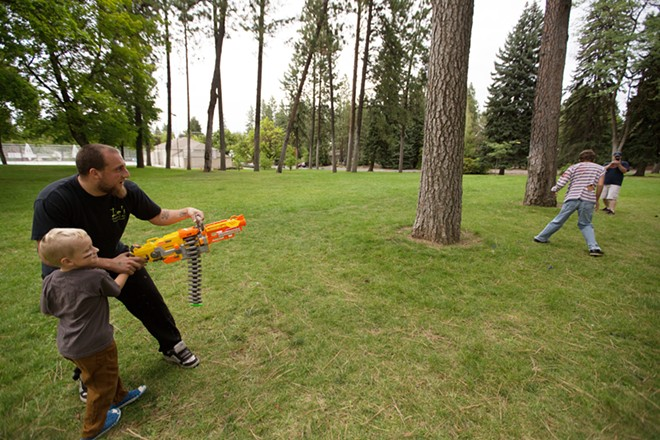 Race participant Justin Krauss, left, helps his 6-year-old son Dakota shoot a zombie. - YOUNG KWAK