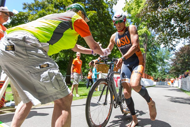 Ray Fiori, right, hands his bike to Ron Lahner. Fiori finished in 9:30:23 and 13th place overall at the Coeur d'Alene Ironman. - MATT WEIGAND