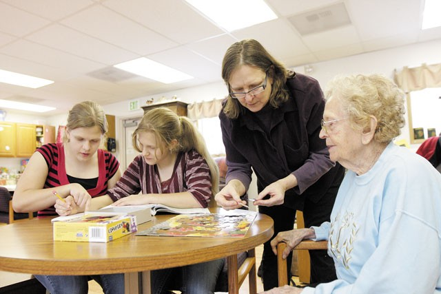 Renee Rinderknecht helps her 93-year-old mother, Dorothy Jensen, as her twin daughters do their homework at All Families Adult Day Care Center. - YOUNG KWAK
