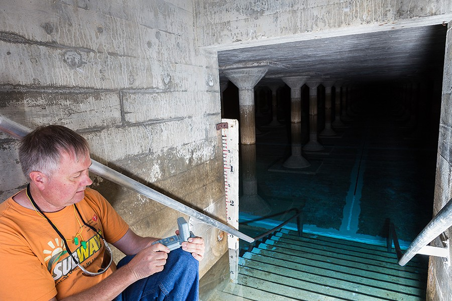 Reservoir provides welcome relief down a short flight of stairs. Inside lies 2 1/2 acres of concrete pillars and pristine drinking water on the eastern edge of Spokane's South Hill. No one was allowed within three steps of the water in order to avoid any contamination. The city has in the past hired a specialized diver who would be bleached before entering the water to perform maintenance. Pictured is city employee Eric Schafer performing a weekly chlorine residual test. - STEPHEN SCHLANGE