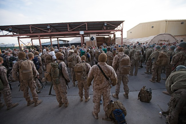 Returning military personnel from combat deployment in Afghanistan watch US Army 391st Military Police Battalion Specialist Seth Schmidt deliver a customs briefing. - YOUNG KWAK