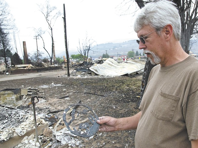 Richard Mathews inspects a decorative metal cutout his son made for him years ago. It's the only keepsake that survived the fire. - JACOB JONES