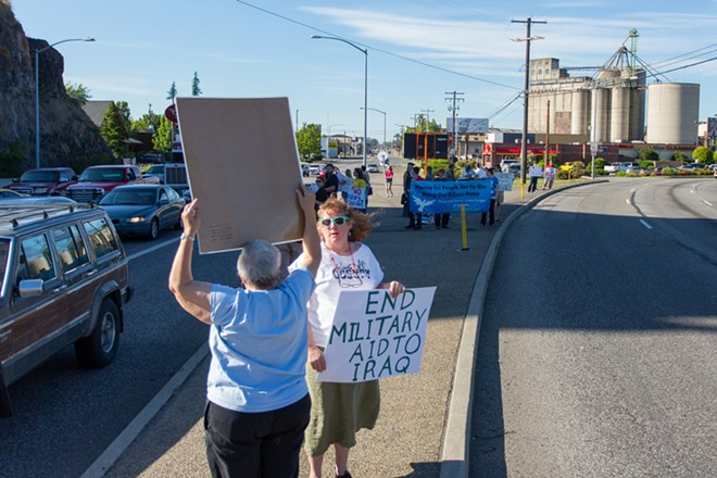 Roughly thirty people protested the threat of bombing Iraq with the Peace and Justice Action League of Spokane on the corner of Division and North River Drive. - MATT WEIGAND