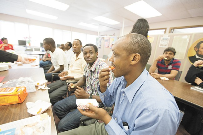 Rwandan refugee Emmanuel Rucyahana, right, tries a carrot during a nutrition workshop at World Relief Spokane. Funding for workshops like this one has been redirected to address immigration at the southern border. - YOUNG KWAK
