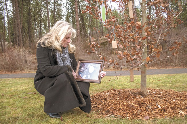 Sandra Carr with a photo of her son, Mark Overland, at his tree-planting memorial service at Mirabeau Park. - SARAH WURTZ