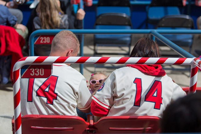 Sean and Rebecka Jenno play with their daughter Anabella while waiting for the first pitch. - MATT WEIGAND