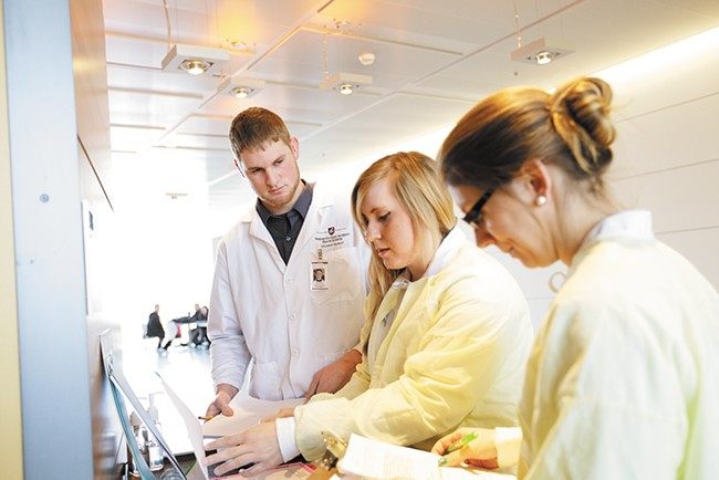 Second-year pharmacy students practice working closely with patients and as part of a team. Here, Kyle Roberts, Julie McCullough and Aubrie Widhalm review a patient chart before entering the simulation lab. - YOUNG KWAK