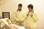 """Second-year pharmacy students work in the simulation lab with a wirelessly operated, programmable mannequin, so realistic that its eyes blink and it can even cry or sweat. Here, Kyle Frazier and Taylor Bertsch interview their """"patient."""""""