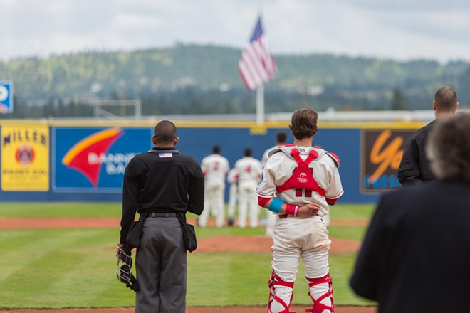 Seth Spivev (11), left, respects the American flag as the National Anthem is played at Avista Stadium. - MATT WEIGAND