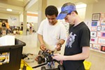 Shaw Middle School 8th graders Habeeb Sabir, left, and Jonathan Murray prepare their robot for MINDS-i competition.
